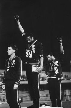 BLACK POWER SALUTE, 1968 Olympics: Tommie Smith, gold (center) & John Carlos, bronze (right) raise black-gloved fists during the American national anthem, Australian sprinter Peter Norman, left, won silver, supported their protest at medal ceremony