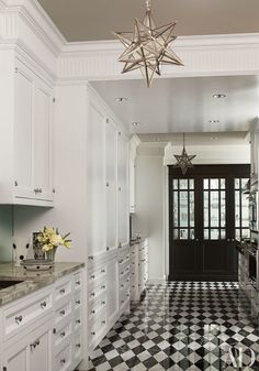 Designer Jean-Louis Deniot outfitted a handsome Chicago prewar apartment with neoclassical-style details and bespoke finishes. In the kitchen, the white cabinetry by Interior Elements sets off the black door and checkerboard floor.