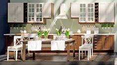 Stylowa, drewniana biało- brązowa kuchnia. Jadalnia kolorystycznie dopasowana do mebli kuchennych, stół brązowy, a krzesła białe. Pomieszczenie ożywiają kwieciste, zielone dodatki || Stylish wooden white-brown kitchen. Dining room colorfully matched to kitchen furniture: brown table, and white chairs. The room revitalizes the flowery, green additions