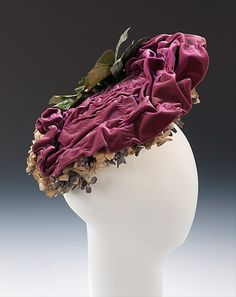 Circa 1905 silk velvet hat, by Camille, French. The sovereignty of the leading Parisian milliners is exhibited in this whimsical creation. While working within the expected media and vocabulary of the time - velvet manipulated to give shape and texture, trimmed at the side and underside with artificial flowers - the designer has beautifully integrated the shape, color and form to give the impression of a large cabbage rose.