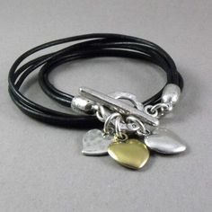 A brand-new design by Danon. This stunning contemporary style bracelet available in black, features three cute heart charms in silver and bronze at the end of the double wrap leather bracelet.