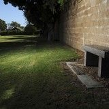 Next to a bench in a pool of light are two unmarked graves among 260 at Ivy Lawn Memorial Park; the final resting sites of those who died while in state institutions including Camarillo State Hospital.