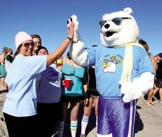 Dawn Stillwell of Collingswood, and a member of Team Frozen Toes, high fives the polar bear as she waits to take the plunge for the first time.