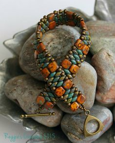 Picasso opaque yellow czechmate tile beads together with picasso opaque olive and copper picasso turquoise superduo seed beads embellished with 8/0 and 11/0 metallic matte bronze toho beads held together with antique bronze triangle toggle clasp. Definitely one of my favorite designs and color combos.