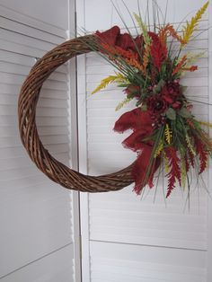 Compact #grapevine #wreath with #redburlap  yellow, orange and red sprays. Green grass and deep red flowers. www.facebook.com/wreathswithareason