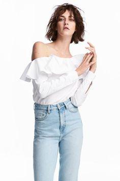 Bluzka z bawełnianej tkaniny z falbanami u góry. Jedno ramię odkryte, długie rękawy z zapinanym mankietem. Prosty krój z rozcięciami u dołu po bokach.