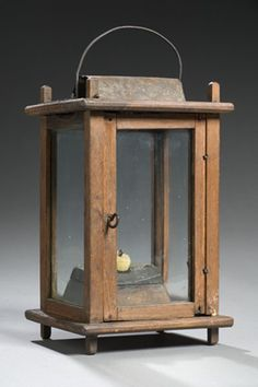 """American, early 19th century, in walnut. The pinned frame holding four glass panes, a sheet iron ventilator and what appears to be a period wooden candleholder; in a natural finish; 6"""" square x 10.75"""" high."""