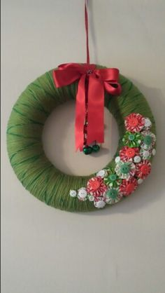Christmas Wreath - made from a polystyrene ring wraped in two shades of green wool and decorated with yo-yos made in christmas fabric and coloured buttons. Finshed off with ribbon and bells
