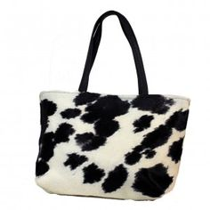 """Black and White Hair on Cowhide tote. Black leather handles. Interior with 3"""" leather top and beautiful pink cotton batik lining. One leather zippered interior pocket and 2 open hand beaded, fabric pockets. Leather strap with brass toggle for easy to find keys. Magnetic closure. 18""""wide x 12"""" high with 5"""" soft bottom."""