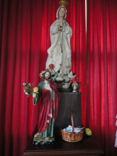 Altar com imagens sacras  e cesto de bilhetes, cartas e pedidos.