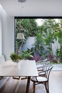 Dining Room decor ideas - small space with bench seating and round back chairs, large open window highlights the lush green patio.