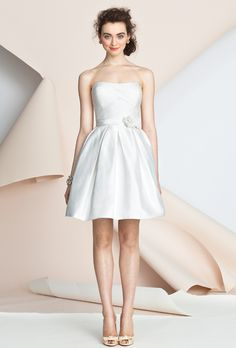Brides: Alyne by Rita Vinieris. Strapless modified pleated short ball gown with soft sweetheart neckline. Bodice is gently draped with a subtle geometric tulle overlay. The waist is accented with a layered belt and a bouquet of textured dupioni and tulle flowers, sprinkled with crystal beading.