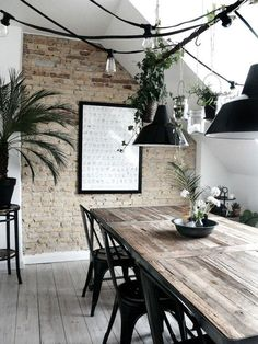 Scandi industrial dining. Love the combination of the texture exposed brick wall, the warm wood and the black metal pendant lights and Tolix chairs. | Decor Trend: Black Metal