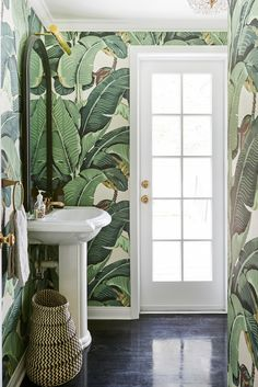 A bright bathroom with banana leaf wallpaper, a white pedestal sink, black mirror, a glass paned door, brass hardware, and dark hardwood floors.