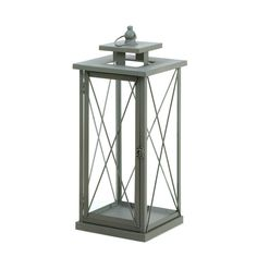 Make a big style statement with this stunning and unique candle lantern. Four glass panels are held by decorative metal framework and topped with a finial and hanging loop.
