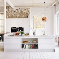 Kitchen. White floors, raw walls and the beautiful copper Tom Dixon lamp.