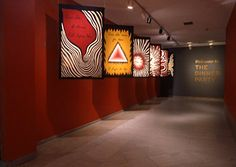 """Six woven banners (5' 6"""" x 3' 6"""" each) hang in procession, welcoming visitors to The Dinner Party. Designed by Chicago, the tapestries repeat the red, black, and gold tones associated with The Dinner Party and incorporate motifs found throughout the piece, such as triangular, floral, and abstracted butterfly forms. After painting the images on paper and selecting the thread colors, Chicago transferred her designs to graph paper, creating cartoons"""