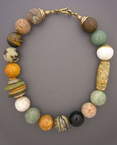 Diversity and color. Stone beads made from agate, onyx, jasper, tigers eye,  and jade. A long carved serpentine bead. Discs made from jade, turquoise,and other stones. And a fancy bronze hook and eye clasp.