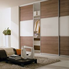 Sliding door system with split panels in walnut wood effect and cream glass. www.harmonymadetomeasure.co.uk
