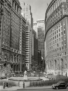 """December 1941. """"Buildings on Lower Broadway, New York."""" The park is Bowling Green, whose focal point was a statue of Abraham de Peyster, 17th-century mayor of the city. Arthur Rothstein. Shorpy Historic Picture Archive"""