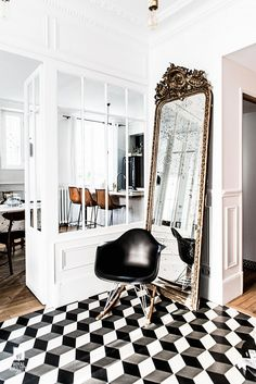 French entryway with a large god vintage mirror, a black chair, and printed tile floors