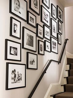 A gallery wall of framed family photos up the entryway  staircase looks extra-chic in black and white!