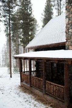 Cabin with veranda. Snow falling on the roof and eves. Skinny pines in surrounding forest. Thick log walls.