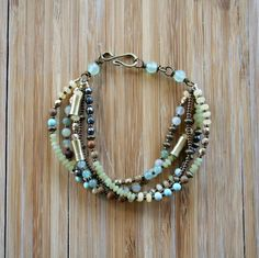 The Willow Bracelet is composed of Five Strands of Sea Green Jade, Pale Peridot Jade, Hematite, Picture Jasper, Lemon Jade, Brass Tubes, Turquoise Jasper, Antique Brass Saucers, and Gold Czech Glass, $60 by SimonandRuby.