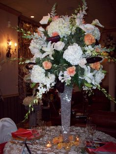 A mixture of white hydrangeas, casablanca lilies, vandella roses, white calla lilies, white snapdragons, white dendrobium orchids with pops of orange roses. Elegant for anytime of the year. Distinctive Floral Design Mineola, NY 516.742.4800
