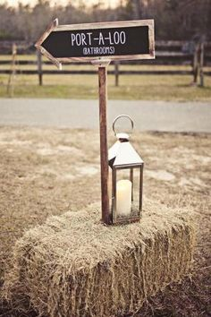 Cute way to do signage... to restrooms & to the reception & the speakeasy setup. Chalkboard sign held up by hay bale points the way.
