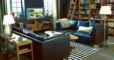 IKEA Stockholm Rand rug, bookshelf, ladder, white lamp, black leather couches, wooden side table