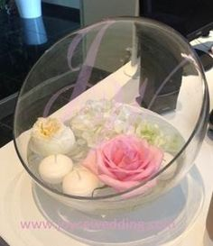 White hydrangea.. White garden roses..and pink roses with floating candle on water in vase is cute and unique