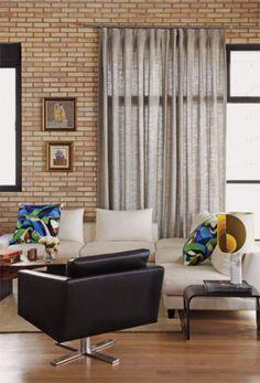 Em harmonia com a parede de tijolos à vista, cortinas de linho (Odair Confecções) filtram o excesso de luz. A poltrona preta de couro (Montenapoleone) entra no clima que permeia a decoração, pontuada por base neutra.