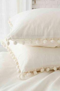 White bed linens with pom pom balls