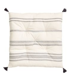 Natural white/striped. Seat cushion in unbleached cotton fabric with a printed pattern. Tassels at corners. Polyester fill. Thickness 1 1/2 in.