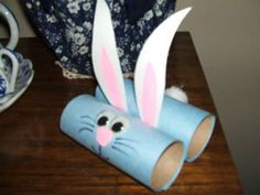 Kids will love seeing these adorable bunnies adorn your holiday table. Roll equal lengths of colored paper around two cardboard tubes and glue ends. Glue the tubes together as shown in photo. Cut out two matching ears, color the inside of ears pink and glue between tubes.