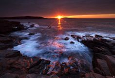 The suns rays strike the rocky coast of Acadia National Park, in Maine, USA.