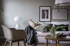 The gorgeous scandinavian living room is just the right mix of minimal and cosy | Stylist Emma Ficher stuck to a colour palette to keep the space feeling harmonious | white linen sofa and designer lighting and chair | the sofa is an IKEA Karlstad sofa with a Bemz slipcover in Absolute White Rosendal linen