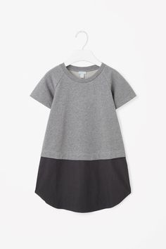 This dress is made from a jersey t-shirt with a skirt in a contrasting cotton material. A casual style, it has a round neckline, short raglan sleeves and a neatly pinned hemline.