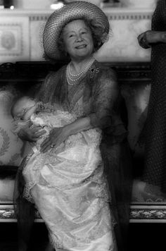La reina Isabel de Reino Unido (reina madre), con su bisnieto el príncipe Guillermo de Gales en sus brazos.