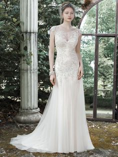 Sundance Wedding Dress | Maggie Sottero A dramatic illusion back and illusion bateau neckline, adorned with glimmering metallic lace appliques, make a statement in this glamorous A-line wedding dress, accented with lovely tulle skirt. Finished with covered buttons over zipper closure.