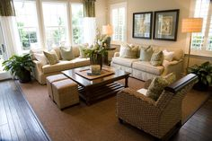 Contemporary living room design with two matching off-white sofas loaded with white and soft green pillows.   One wicker armchair.  Square coffee table supplemented with two small wicker ottomans.