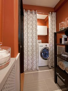 Because they're already plumbed, bathrooms can be a great place to tuck in a washer and dryer. Natalie Sheedy of Natalie Sheedy Interiors took advantage of this long, narrow space, installing appliances at one end and screening them off with a pretty curtain. Extending the deep orange paint color into the laundry area makes it feel of a piece with the rest of the room.