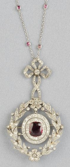 An Edwardian Platinum, Ruby, and Diamond Pendant. Bead-set with a cushion-cut ruby framed by old single-cut diamonds, and within an old single- and rose-cut diamond garland, and suspended from a bow, millegrain accents, together with a white gold chain with bezel-set rubies. Pendant length 2 1/4 in. #Edwardian #pendant