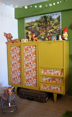 mustard yellow cabinet with vintage wallpaper.