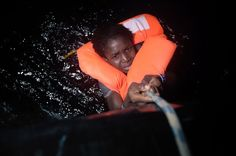 A migrant holds onto a rope during a rescue operation some eight nautical miles off Libya's Mediterranean coastline