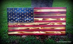 "Simply stunning! Show your American pride or patriotism with this 24"" tall by 48"" wide solid wood flag. Both sides are fire scorched, reinforced back and clear coated on both sides for durability. Comes complete with hanging hooks on the back. Your choice of the American flag, any branch of our Military, Law Enforcement and Fire! Support all of our first responders.  First responder series is finished with a subdued black stain, a red or blue line, and a glossy clear coat finish."