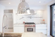 White and chrome kitchen with marble slab backsplash
