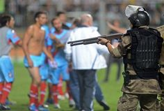 A Brazilian anti-riot police officer aims his pellet shotgun to Argentinas Arsenal soccer players at the end of the Copa Libertadores soccer match against Brazils Atletico Mineiro in Belo Horizonte, Brazil, Wednesday, April 3, 2013. Atletico Mineiro won 5-2. (AP Photo/Eugenio Savio)