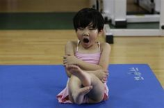 A girl yawns as she practices before a diving training session at a training center in Beijing, July 26, 2011.  REUTERS/Jason Lee
